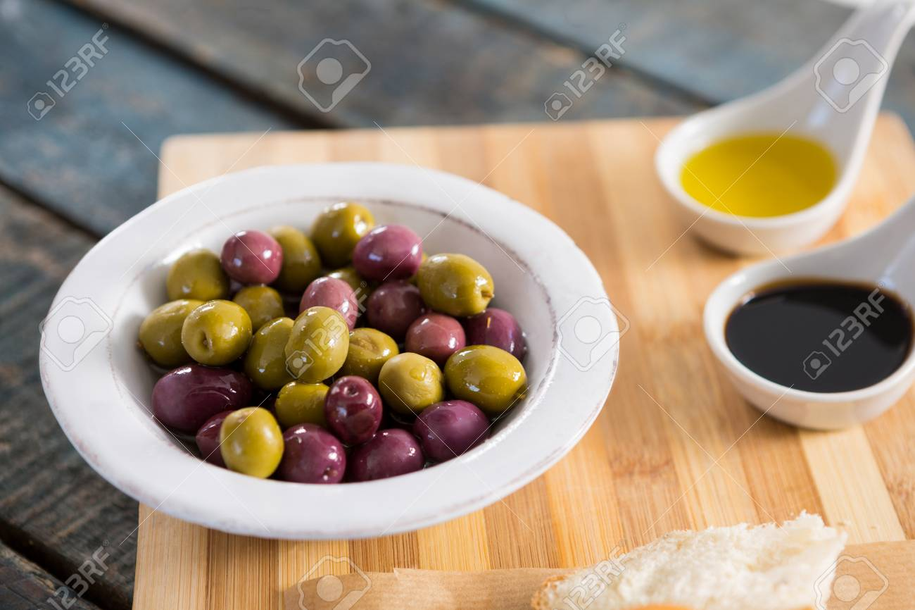 a5cae3bc6376 Close-up of marinated olives with olive oil on chopping board Stock Photo -  81809178