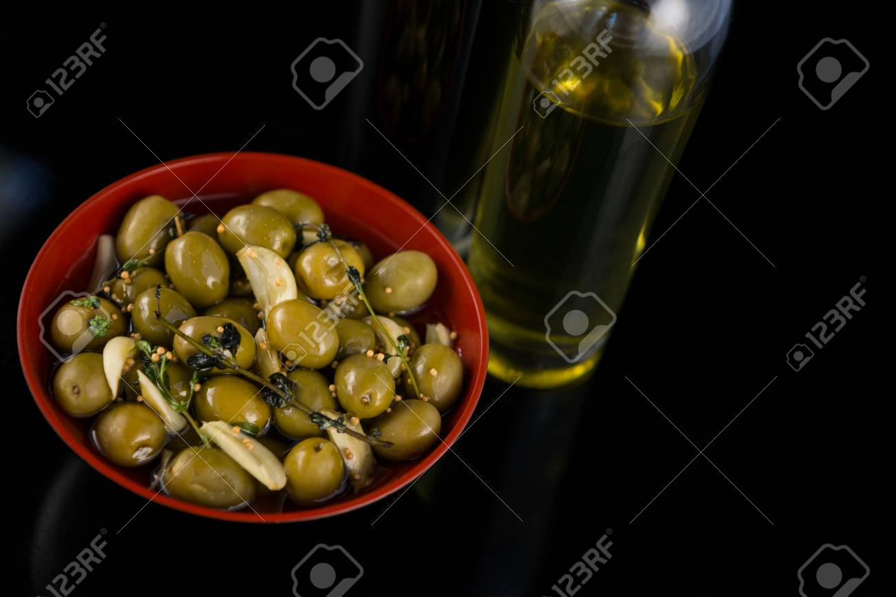 05f4e4a9ffa3 Close-up of marinated olives with olive oil and balsamic vinegar bottle  against black background