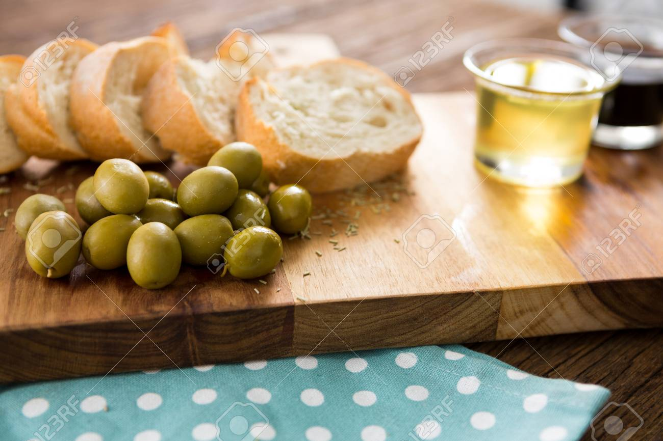 48c1149debeb Close-up of olive oil with olive and bread kept on chopping board Stock  Photo