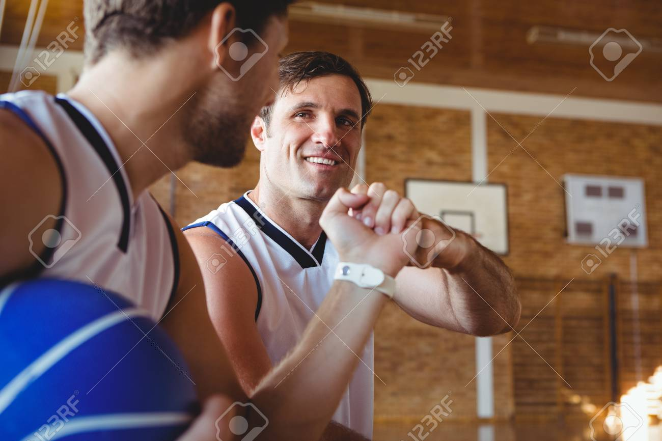 Smiling basketball players doing fist bump while sitting on bench