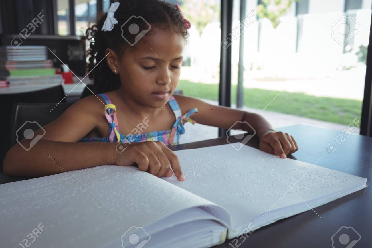 Close up of girl reading braille at desk in library - 82353689