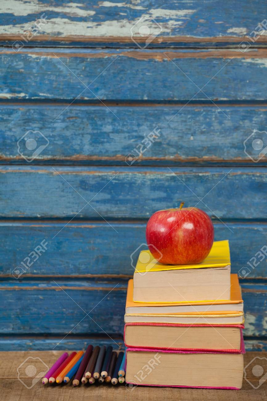 Stack Of Books, Apple And Color Pencils Against Blue Wooden ...