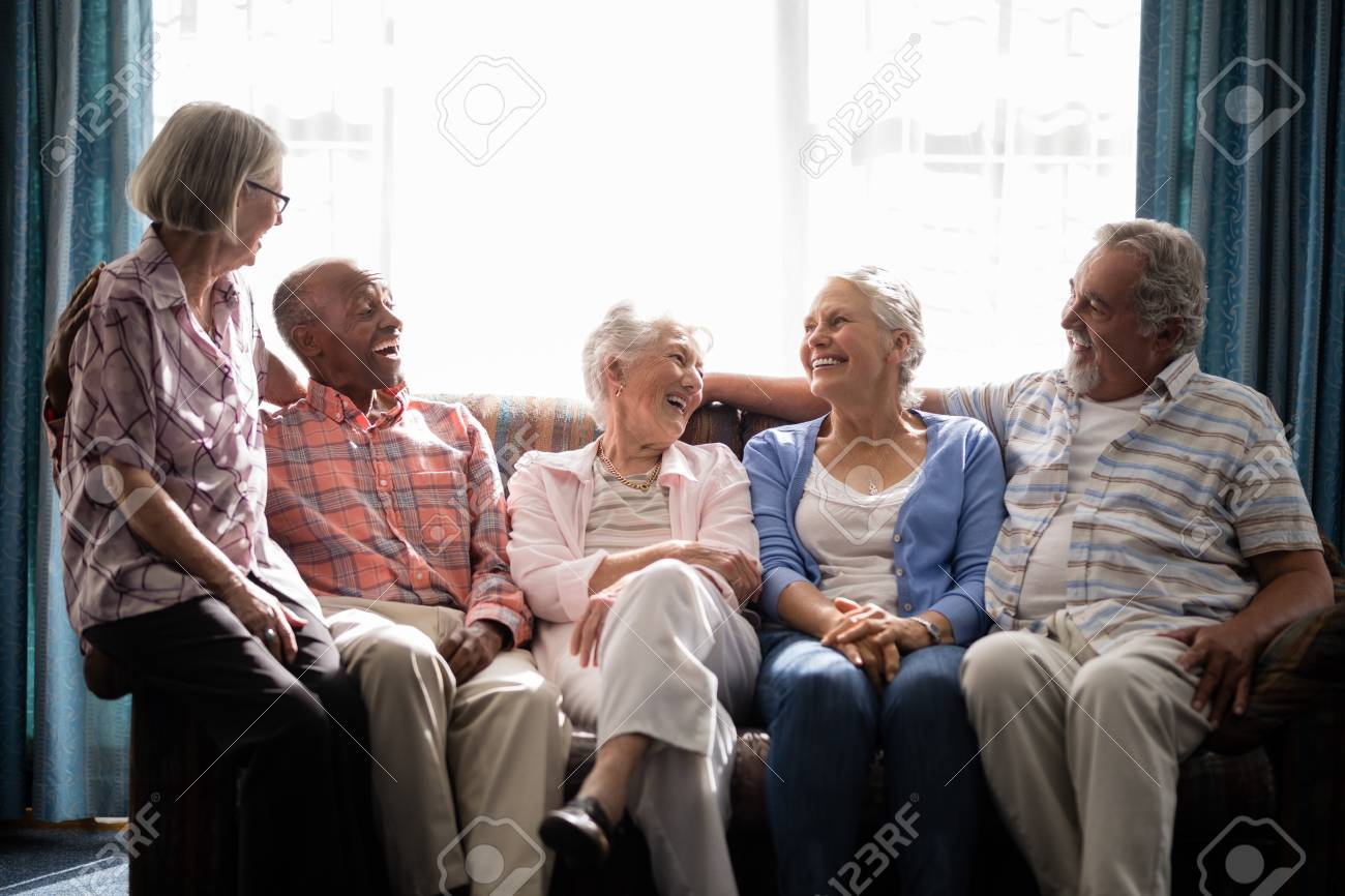 Smiling senior friends talking while sitting on couch against window in nursing home - 82678128
