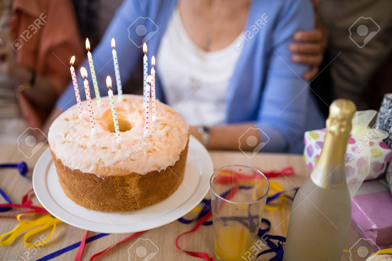 Close Up Of Candles On Birthday Cake With Senior People In