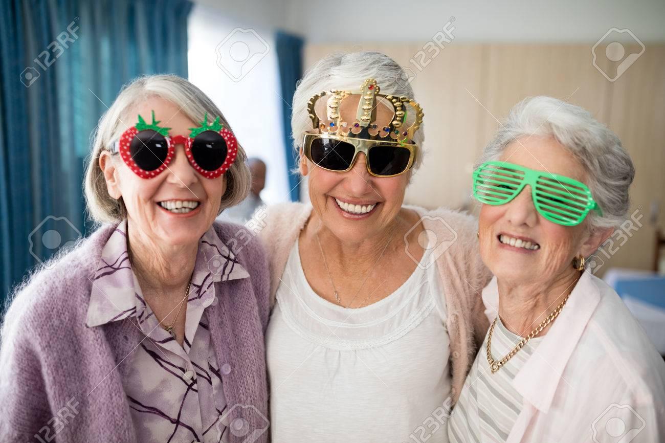 Portrait of smiling senior women wearing novelty glasses at nursing home - 82683222