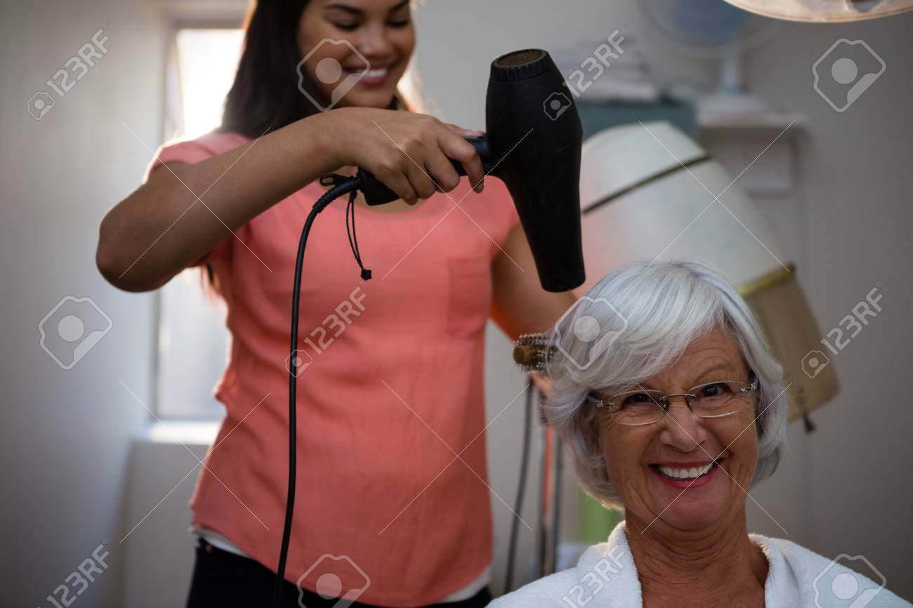 Beautician drying senior woman hair in salon - 83562514
