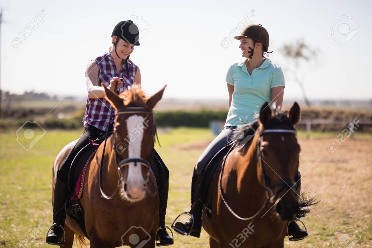 Full Length Happy Female Friends Talking While Horseback Riding Stock Photo Picture And Royalty Free Image Image 83636047