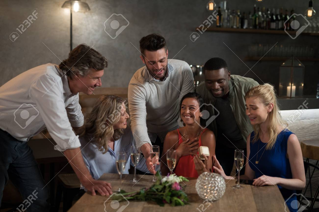 Woman Receiving Birthday Gift Form Her Friends In Restaurant Stock