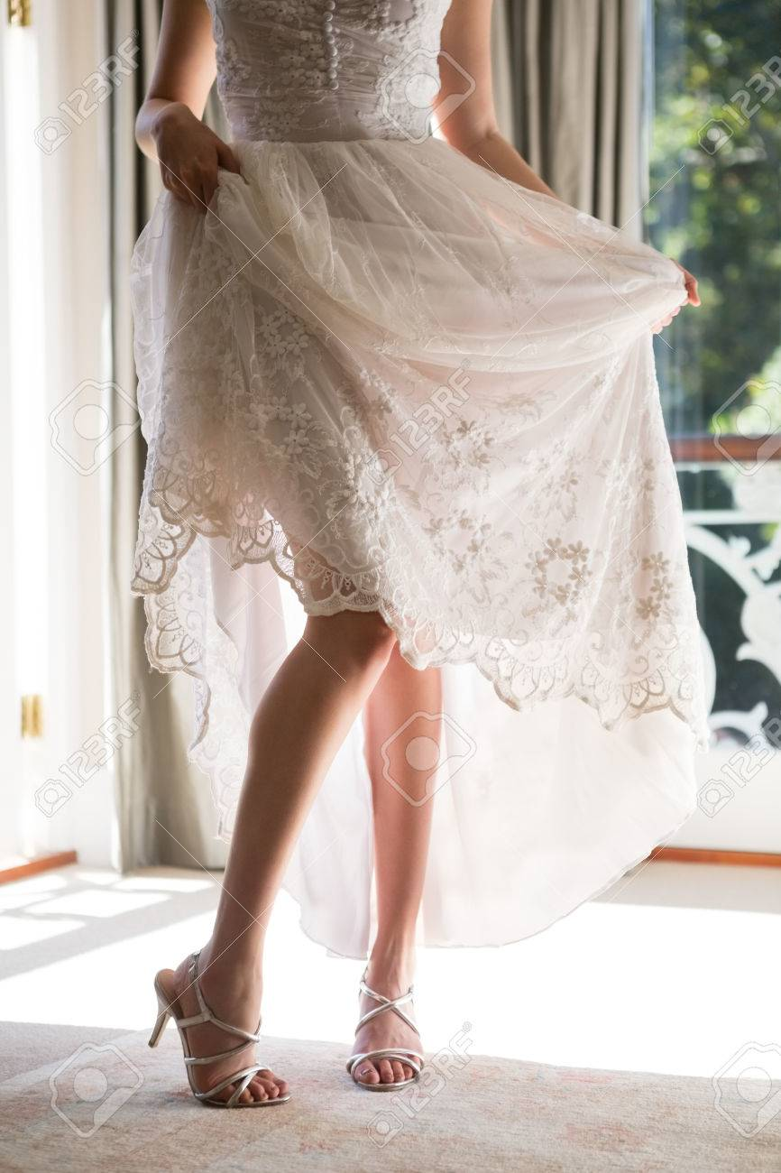 276457f05 Low section of bride in wedding dress and sandals standing on floor at home  Stock Photo