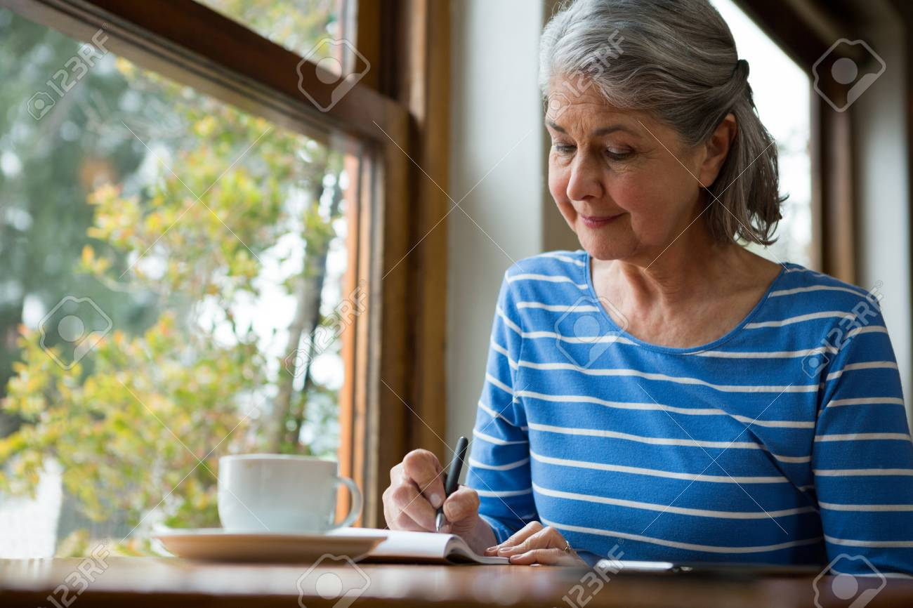 Senior woman writing in a diary in cafe - 88472723