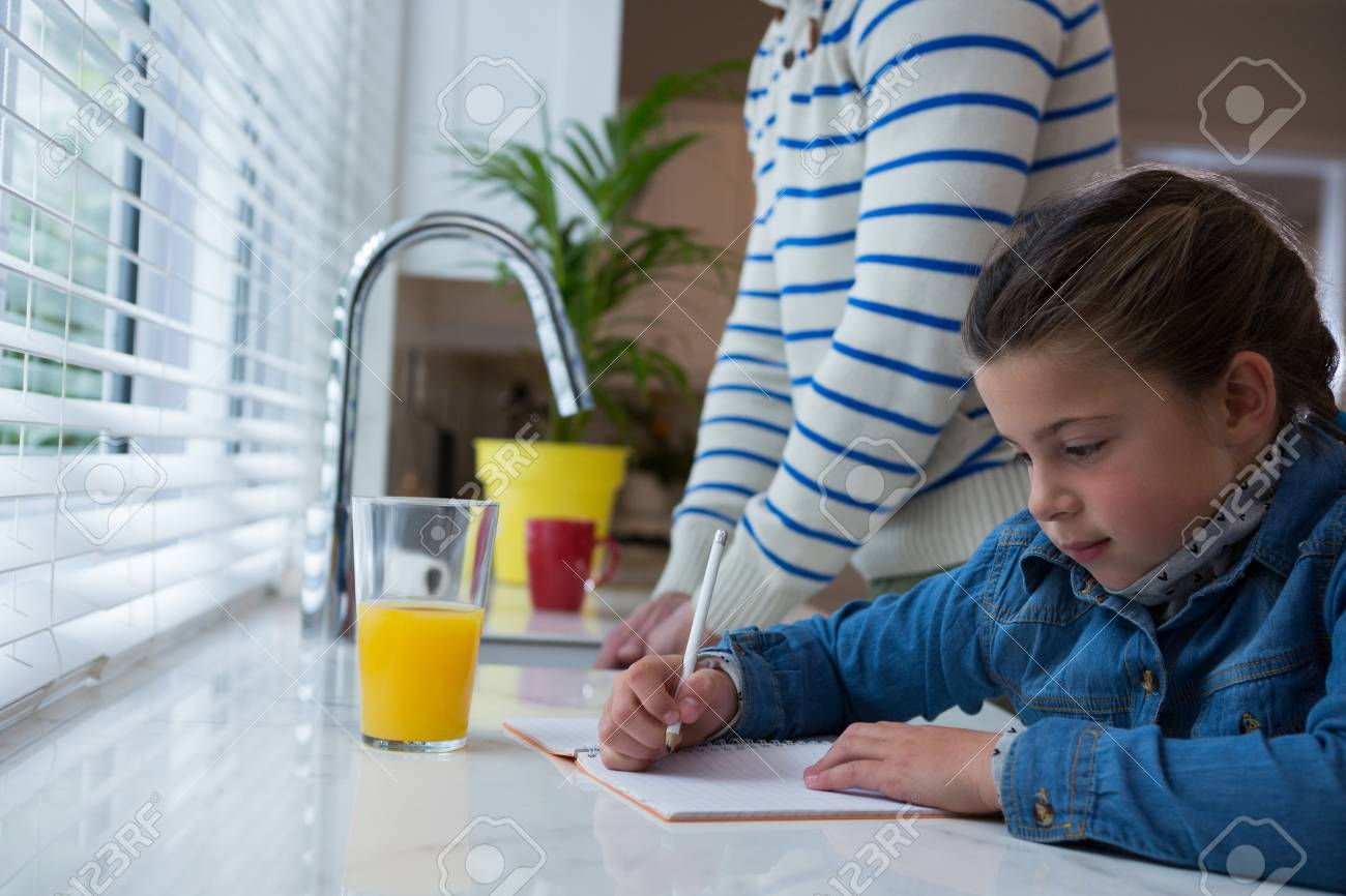 Cute Girl Doing Homework In Kitchen At Home Stock Photo, Picture And ...