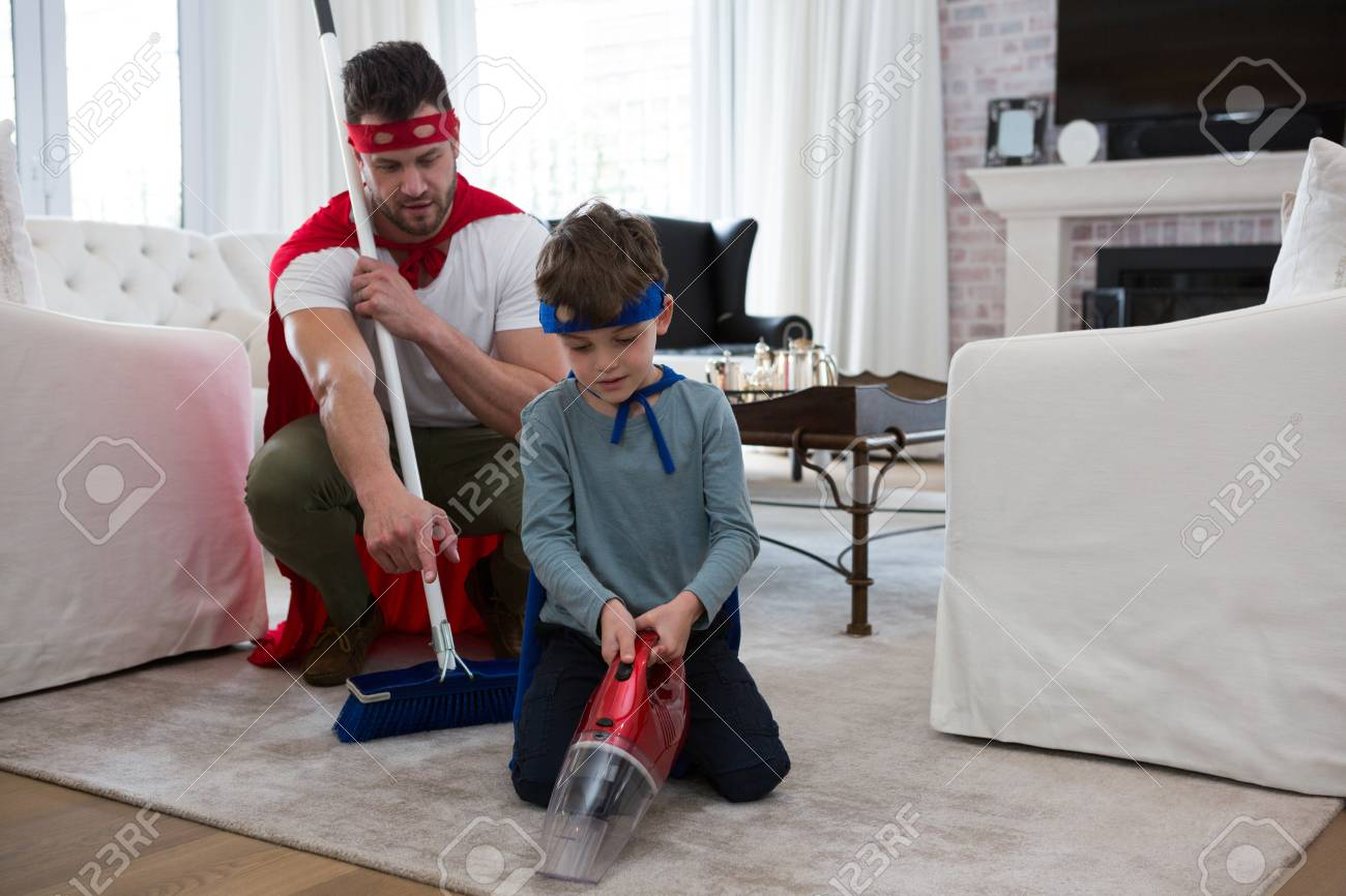 Father And Son Pretending To Be Superhero While Cleaning Floor Stock