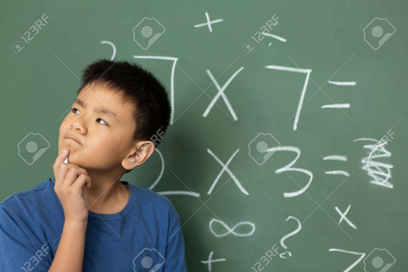 Front view of thoughtful Asian schoolboy doing math on green chalkboard in a classroom at elementary school - 121813078