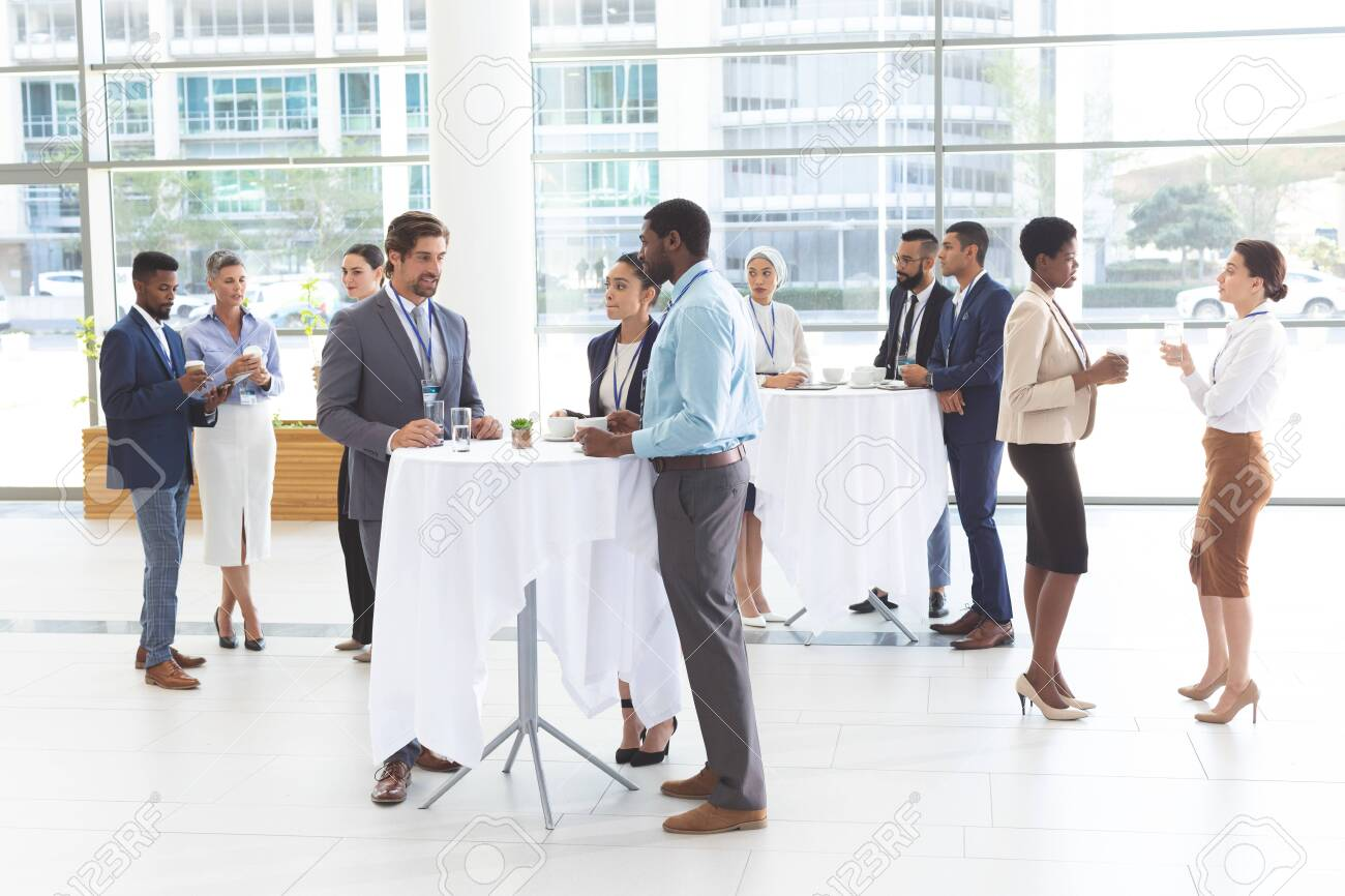 Front of view of diverse business people interacting with each other at table in office lobby - 121810990