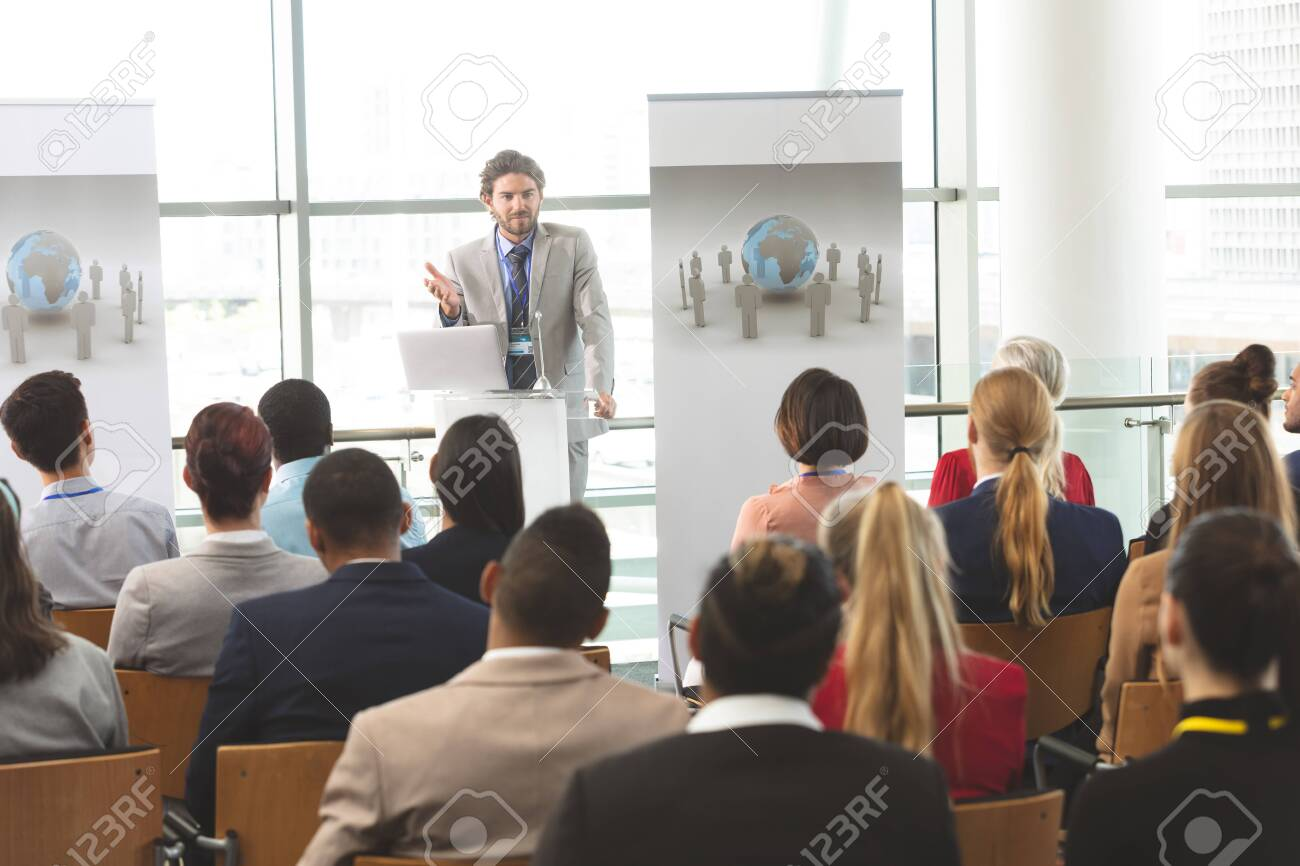 Front view of Caucasian businessman with laptop speaks in front of diverse crowd of business people at business seminar in office building - 121810991