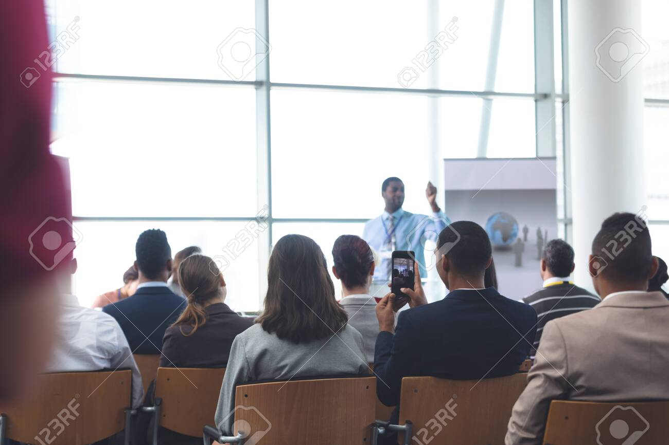 Rear view of young African-Aerican businessman clicking photo with mobile phone in a business seminar - 121792505