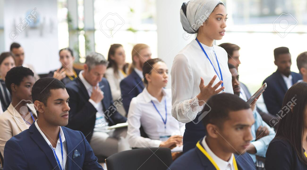 Side view of young mixed race businesswoman asking question during seminar in office building - 122225114