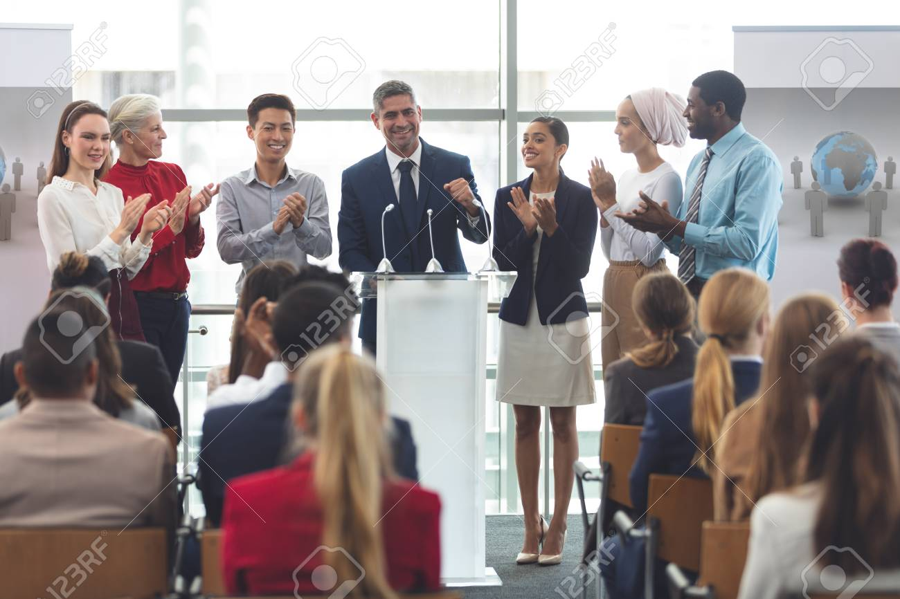 Front view of diverse group of business professionals standing on podium while speaking in front of business people at business seminar in office building - 122224527