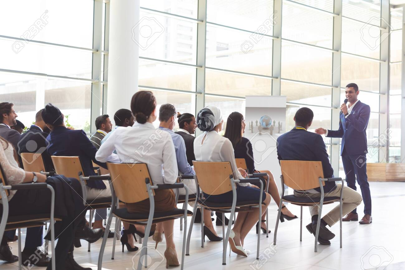 Front view of handsome mixed-race businessman speaking at business seminar with diverse business people listening to him at conference - 122224022