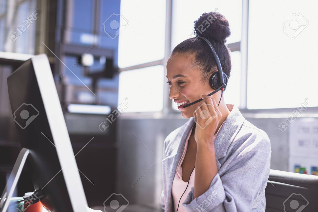 Side view of young mixed-race businesswoman talking on headset while working on computer at desk in the office - 121757240