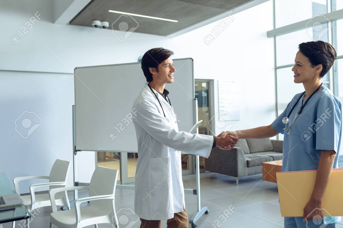Side view of male happy Caucasian doctor shaking hands with smiling female Caucasian nurse in the hospital - 124670137