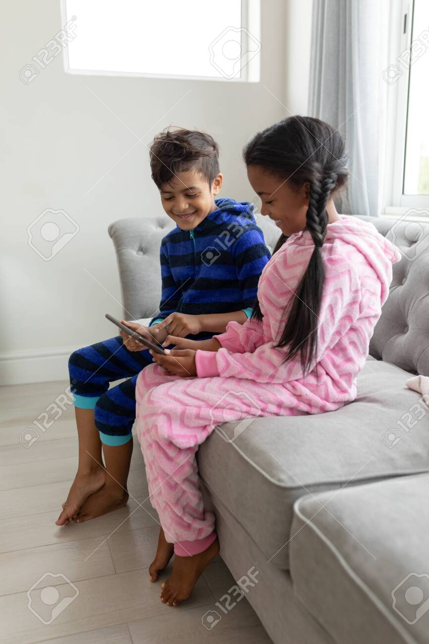 Side view of African american Happy Siblings using digital tablet on a sofa in living room at home - 126117917