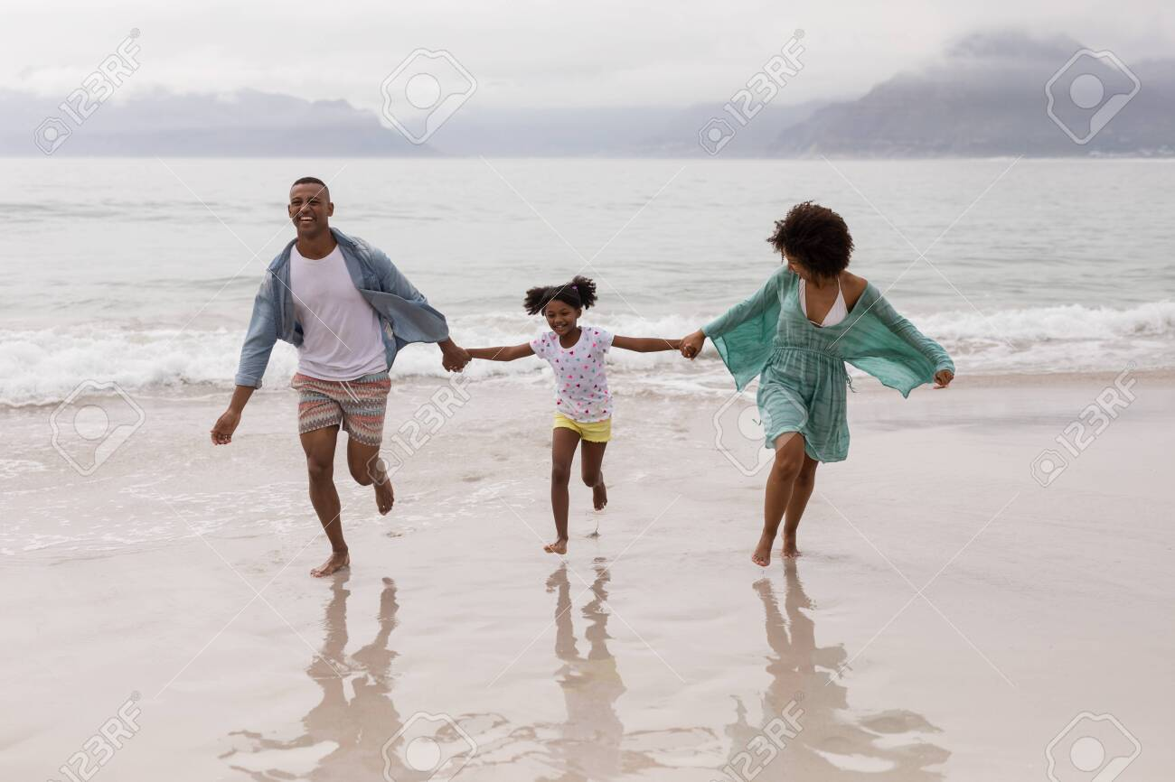 Front view of Happy African american family having fun together on the beach - 126120056