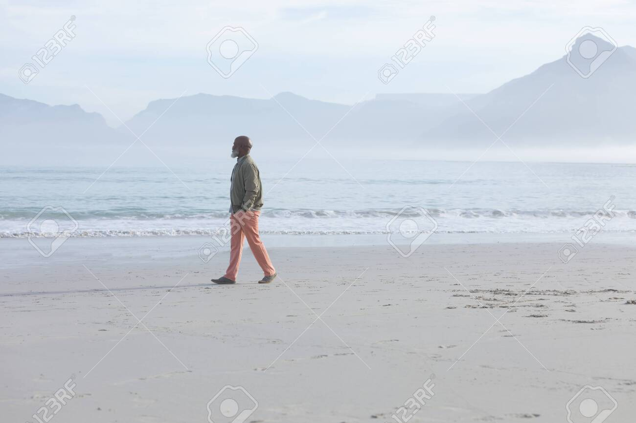 Side view of handsome senior African-American man walking on the beach with his hands in pockets on beautiful day. Authentic Senior Retired Life Concept - 126952881
