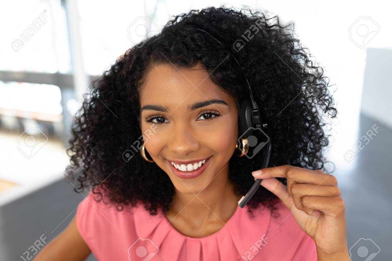 Portrait of African american female customer service executive talking on headset at desk in office. This is a casual creative start-up business office for a diverse team - 126956341