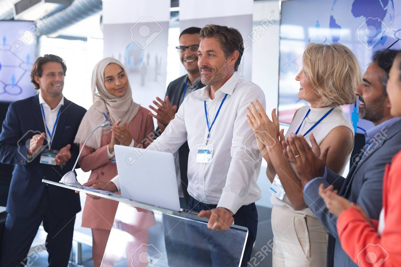 Front view of mature Caucasian businessman standing with diverse colleagues and speaks in a business seminar. International diverse corporate business partnership concept - 127165267