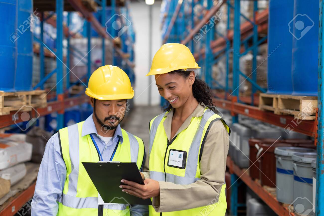 Front view of male and female worker discussing on clipboard in warehouse. This is a freight transportation and distribution warehouse. Industrial and industrial workers concept - 128269903