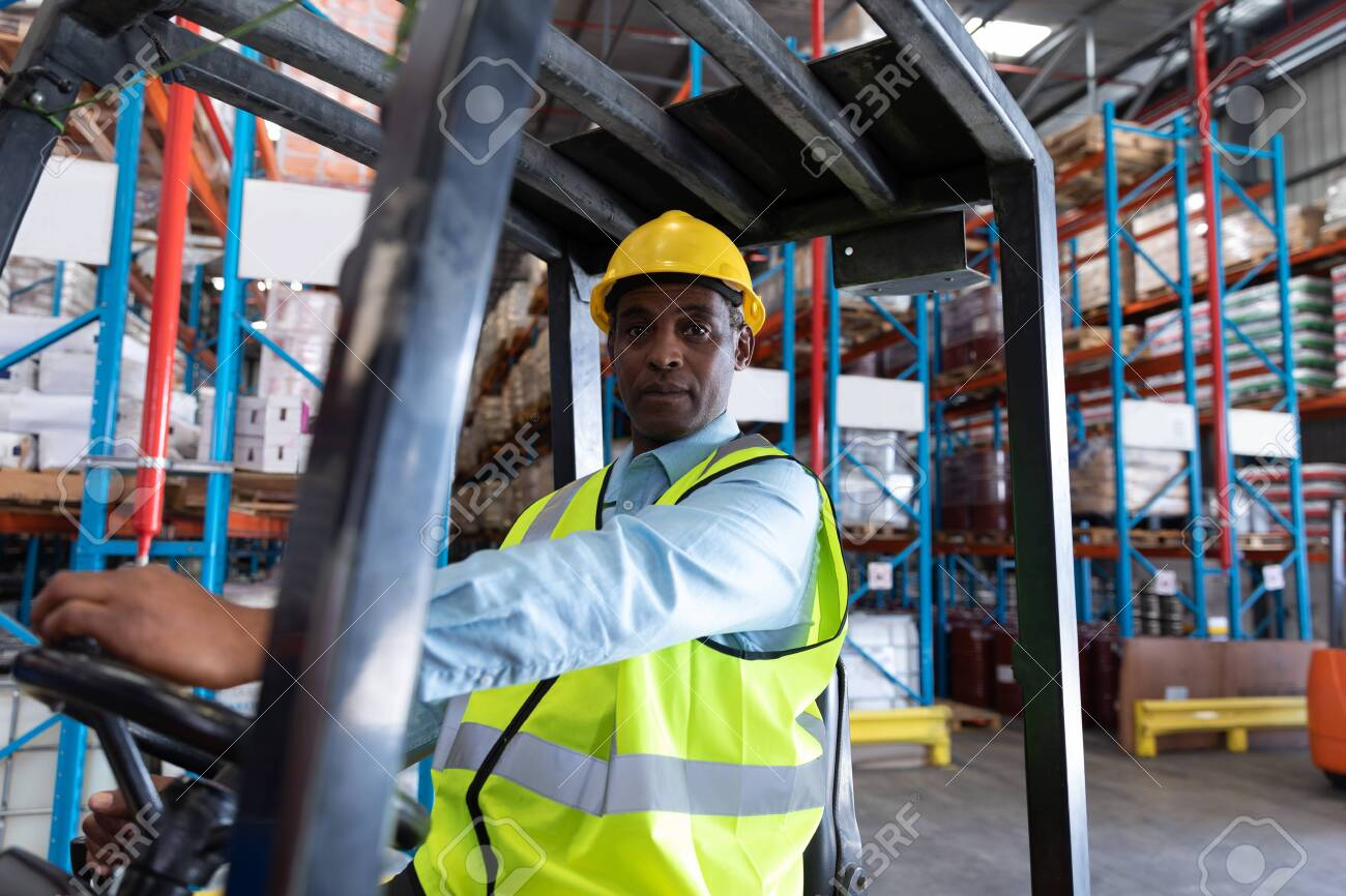 Front view of male worker looking at camera while driving forklift in warehouse. This is a freight transportation and distribution warehouse. Industrial and industrial workers concept - 128270503