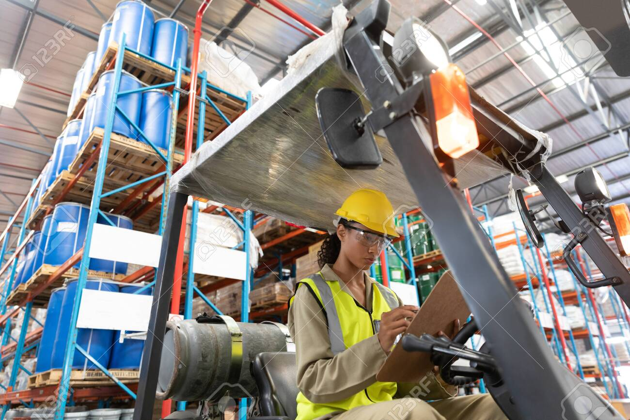 Low angle view of female staff writing on clipboard while sitting on forklift in warehouse. This is a freight transportation and distribution warehouse. Industrial and industrial workers concept - 128270542