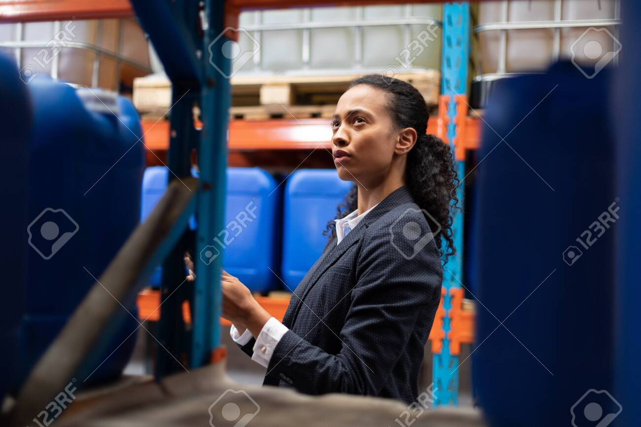 Side view of female manager checking stocks in warehouse. This is a freight transportation and distribution warehouse. Industrial and industrial workers concept - 128270150