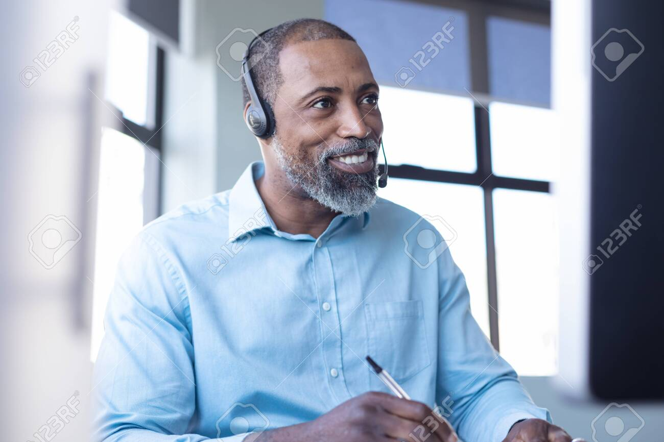 Front view close up of an African American male business creative working in a casual modern office, making notes, smiling and talking on a phone headset - 133884264