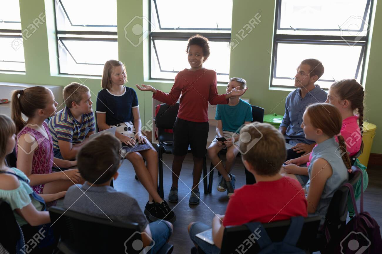 Front view of a diverse group of elementary school kids sitting on chairs in a circle and interacting during a lesson, one African American girl standing and talking while her classmates and male Caucasian teacher sit and listen - 138432103
