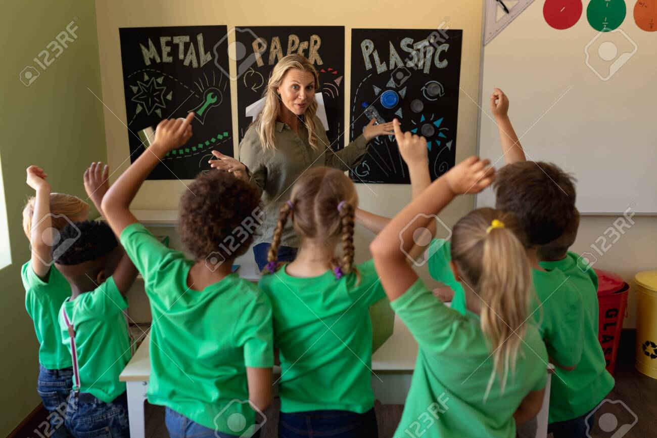 Front view of a Caucasian female school teacher with long blonde hair pointing to a recycling poster and a diverse group of schoolchildren wearing green t shirts seen from behind, raising their hands to answer a question during a lesson in an elementary school classroom - 138539577