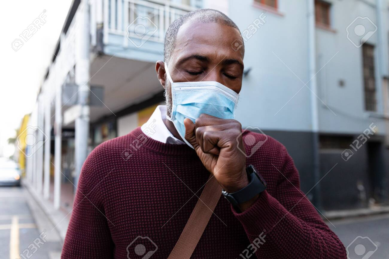 African American man out and about in the city streets during the day, wearing a face mask against air pollution and covid19 coronavirus, covering his face while coughing. - 143110978