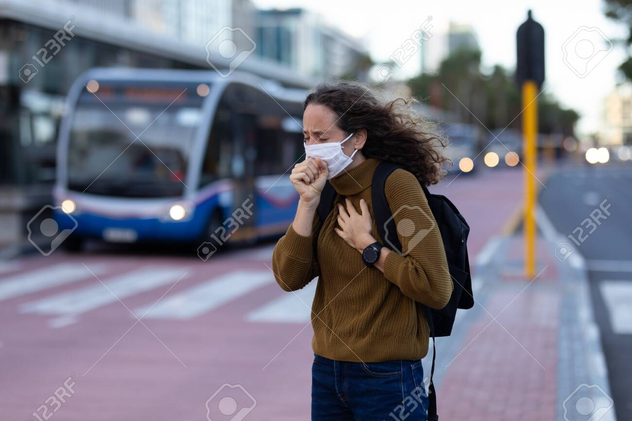 Caucasian woman out and about in the city streets during the day, wearing a face mask against covid19 coronavirus covering her face while coughing - 146214180