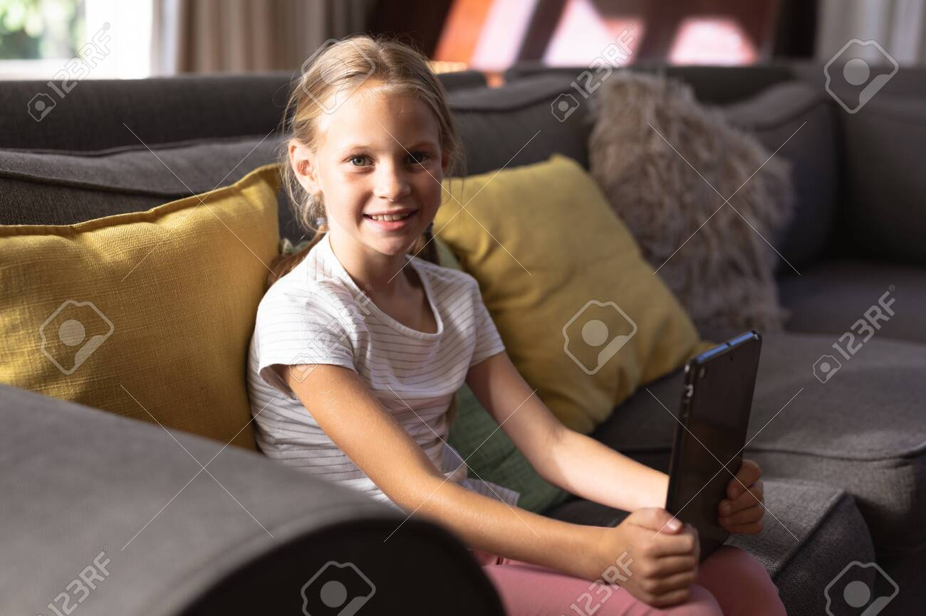 Portrait of a Caucasian girl enjoying her time in a house, sitting on a couch, holding a digital tablet, looking at the camera and smiling, social distancing and self isolation in quarantine lockdown during coronavirus covid19 epidemic, - 147212096