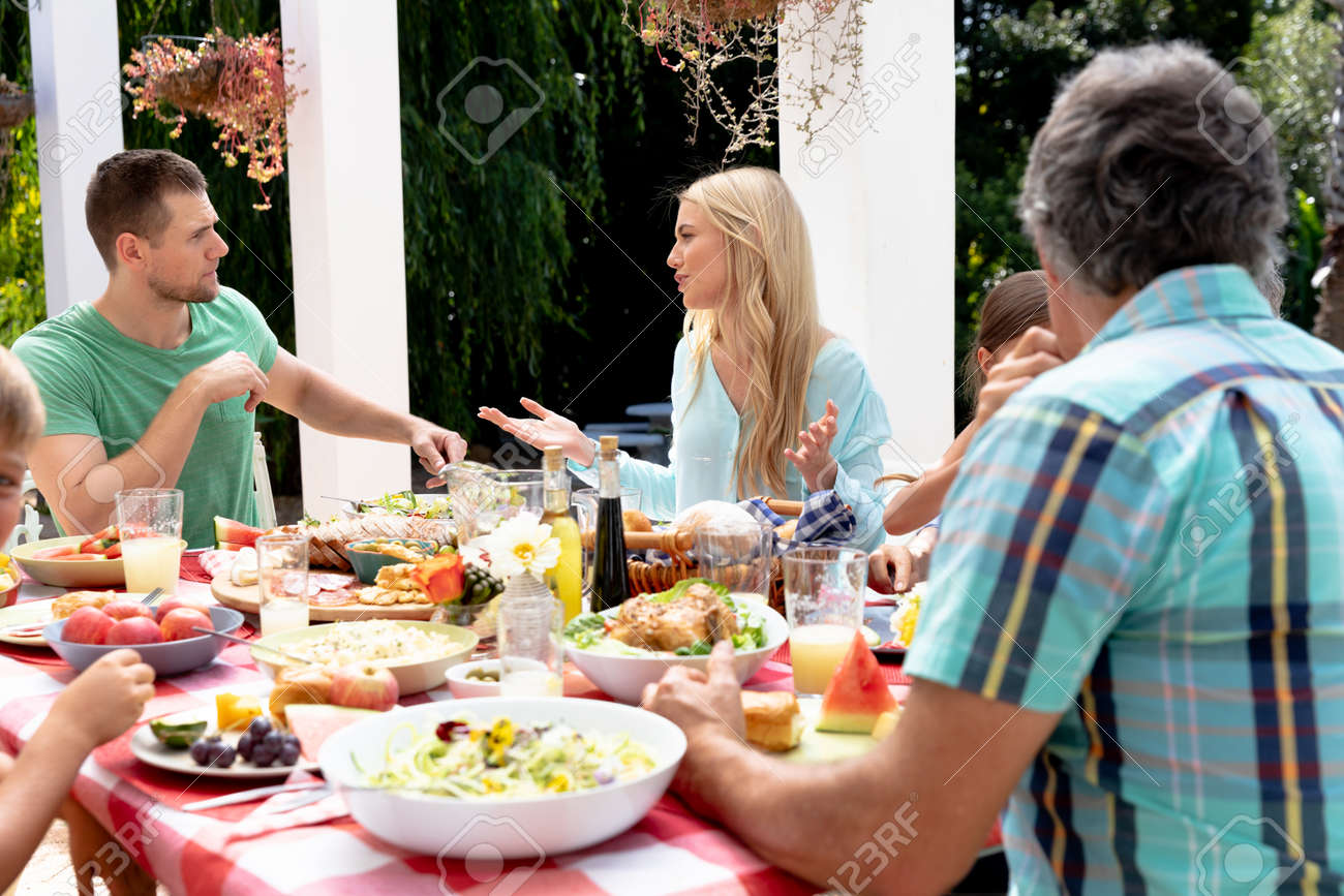 Caucasian three generation family having a lunch in the garden on a sunny day, sitting by a table and interacting. - 147214407
