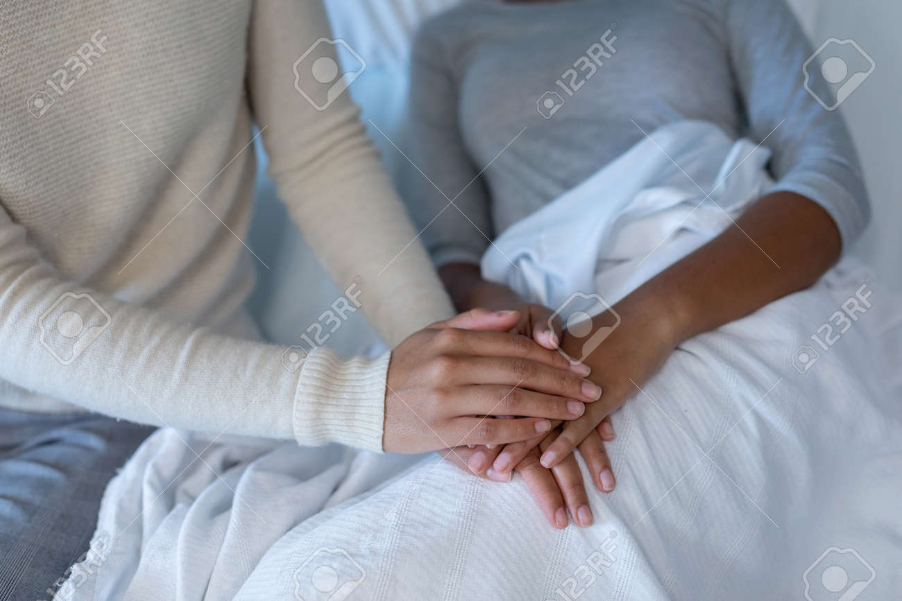 Midsection of mixed race mother comforting sick daughter, sitting on hospital bed holding her hands. medicine, health and healthcare services. - 168527468