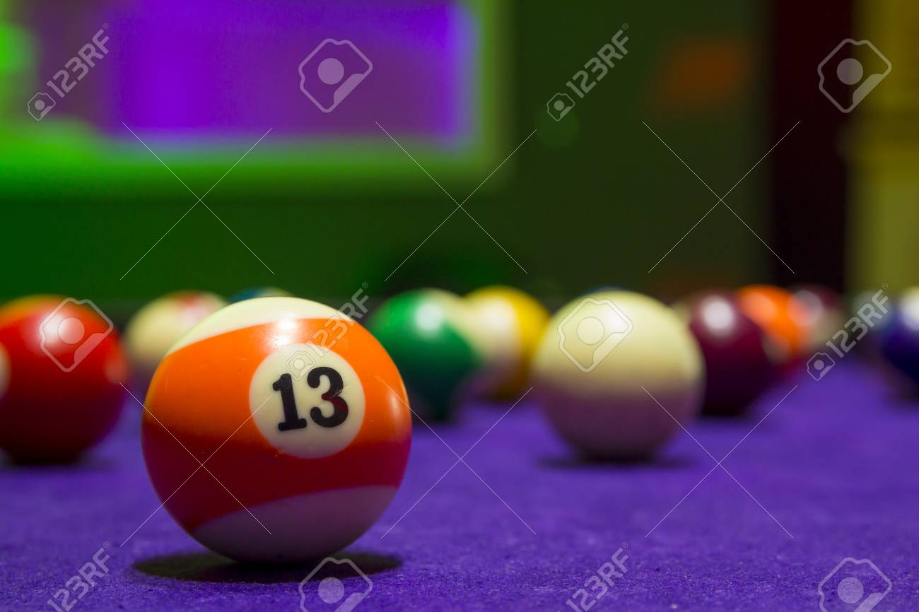 Billiard Balls In A Pool Table. Focus On The Orange Number 13 Ball. Stock