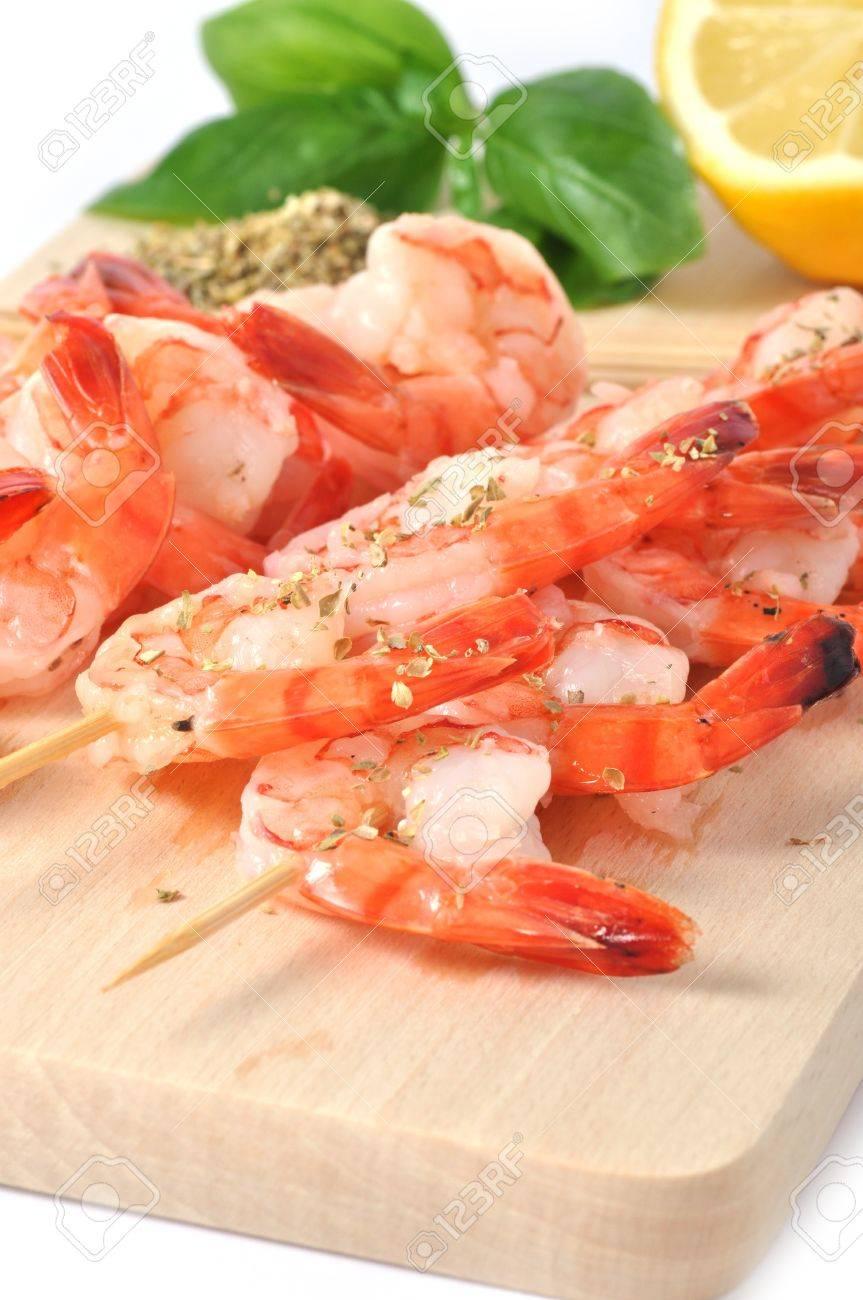 Shrimps, olives, lemon, and basil on board isolated on white background Stock Photo - 8173495