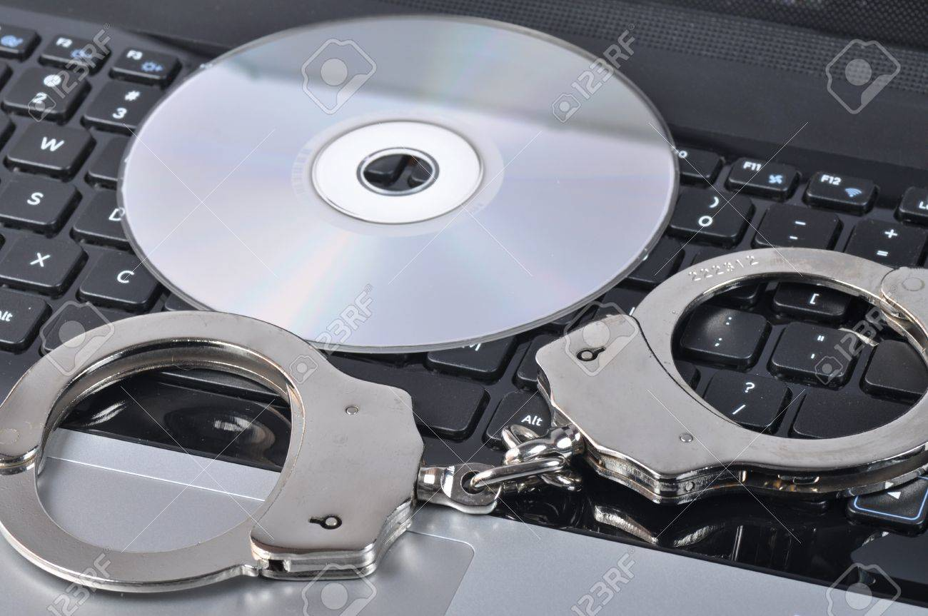 Handcuffs and CD - ROM on laptop Stock Photo - 16533716