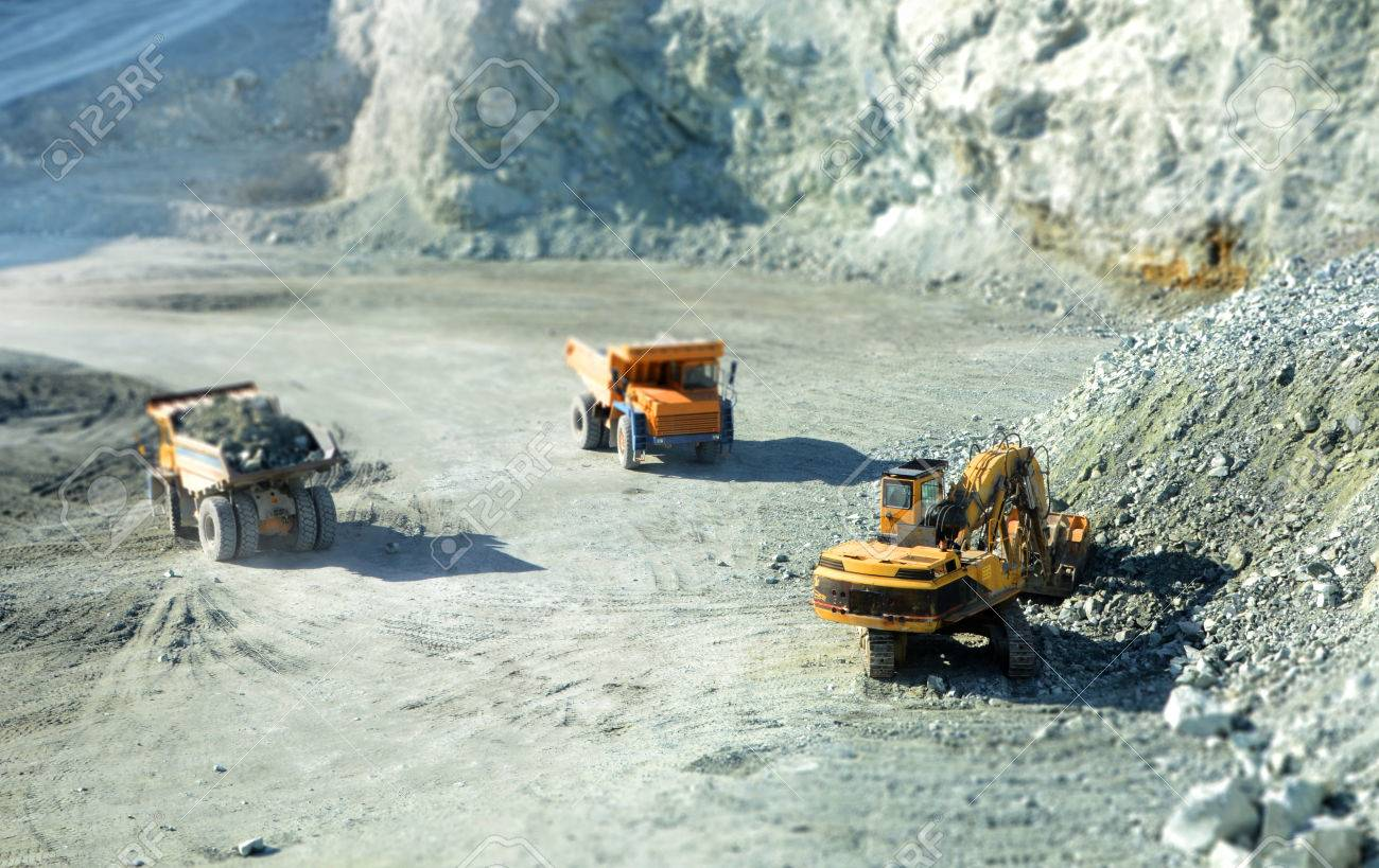 Big yellow trucks in quarry with tilt-shift effect - 38637301