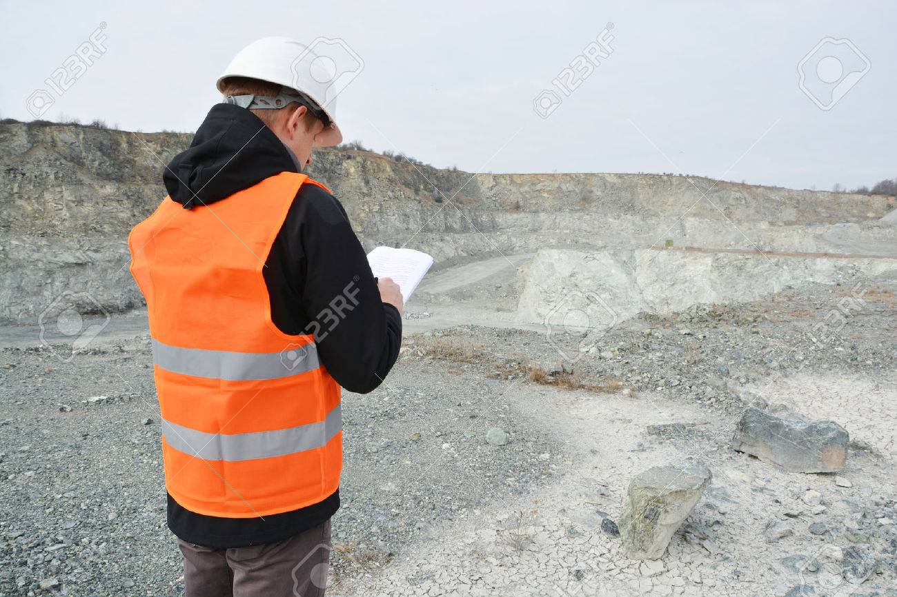 Worker in a helmet and quarry in background - 39542670