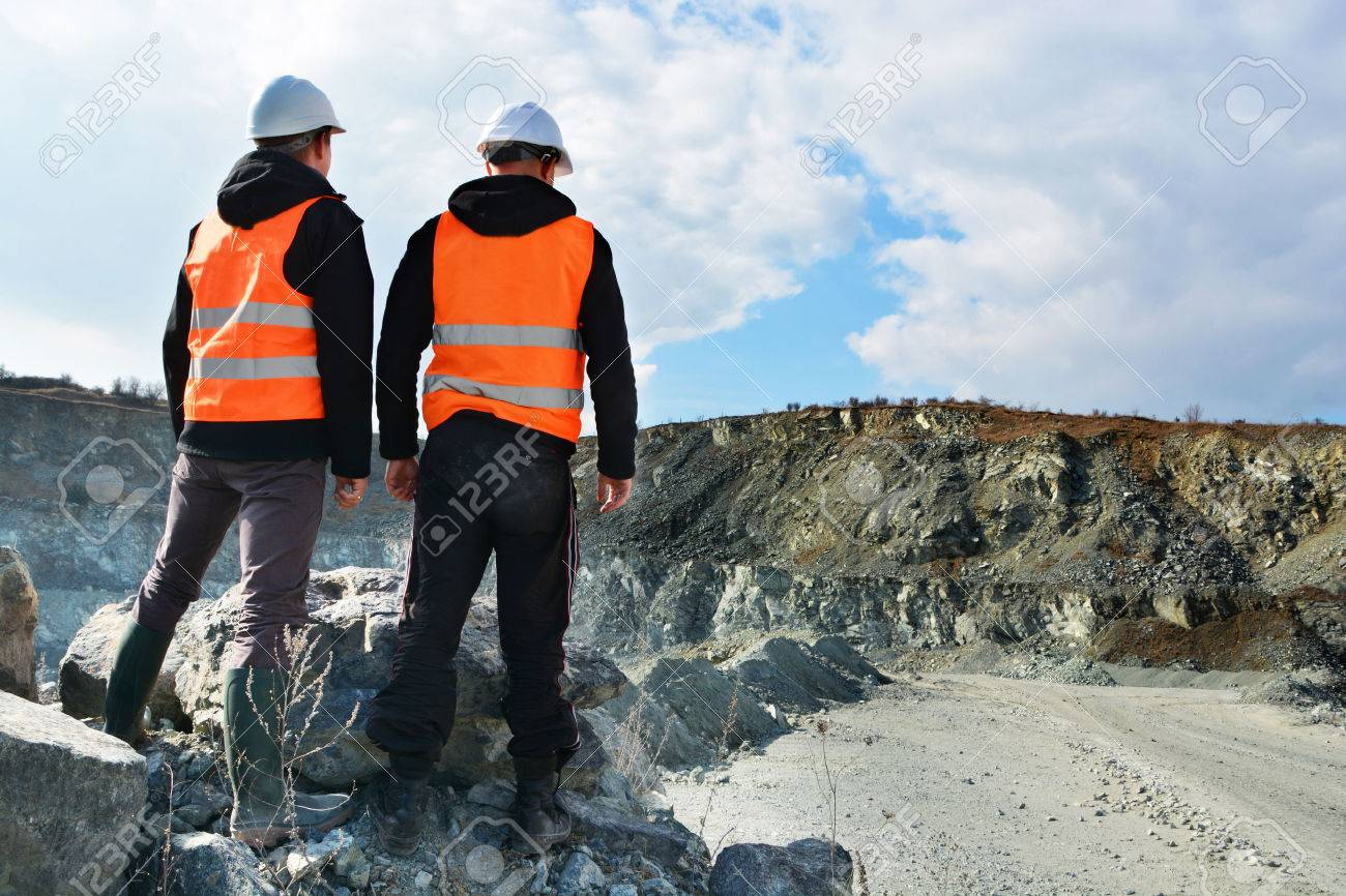 Two workers and quarry in background - 39542673