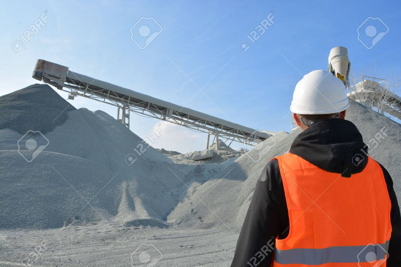 Worker and heavy machine for gravel production in background - 40258605