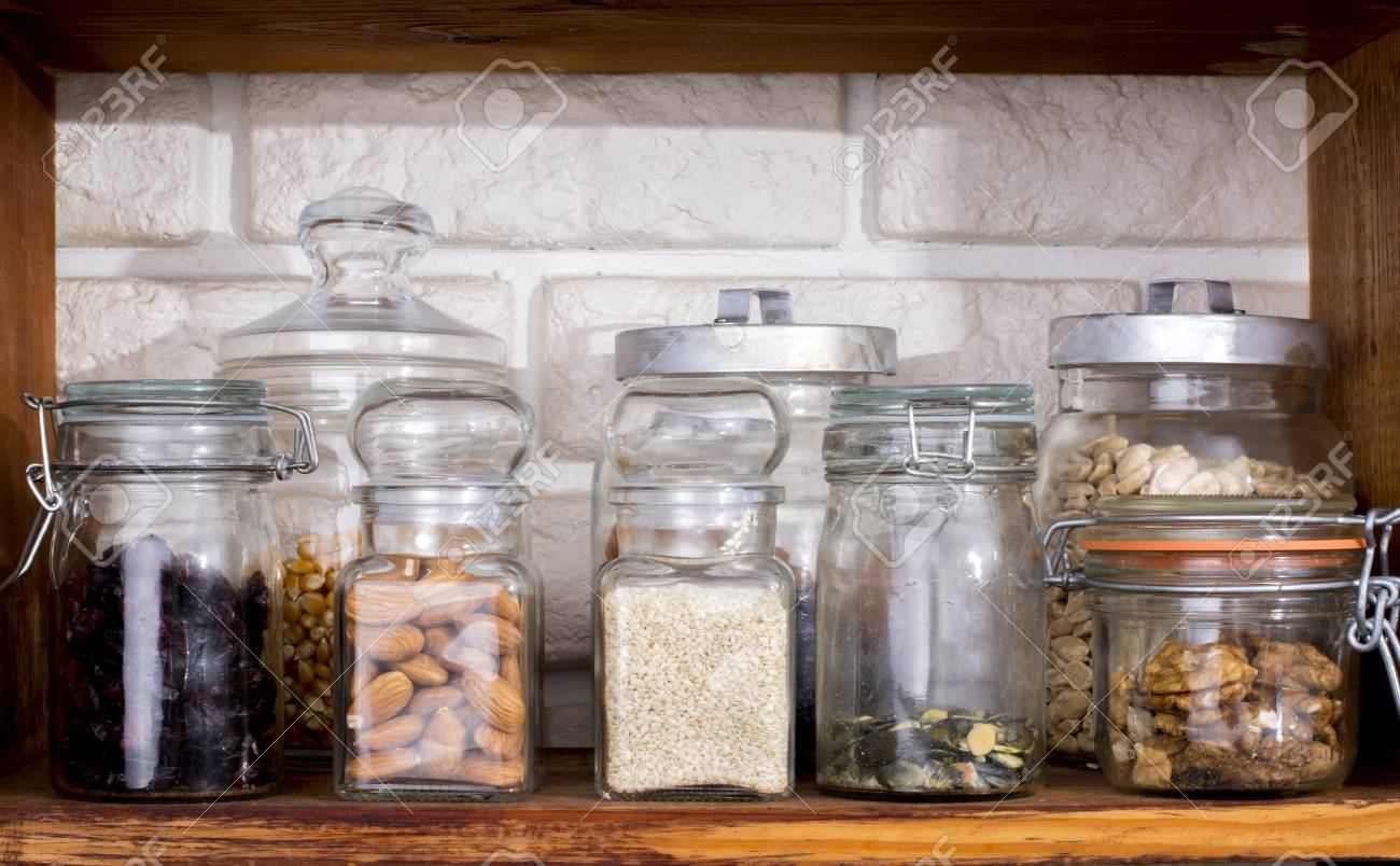 Jars with dried fruits and nuts on shelf - 60069969